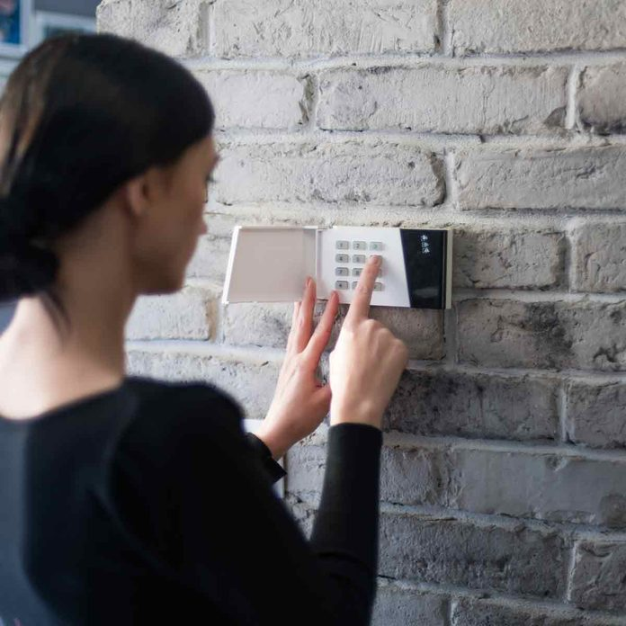 Young-woman-entering-security-pin-on-home-alarm-keypad