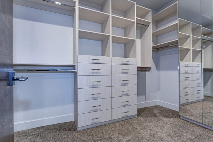 Large walk-in closet lined with built-in drawers, clothes rails and shelving over light brown carpet floor.