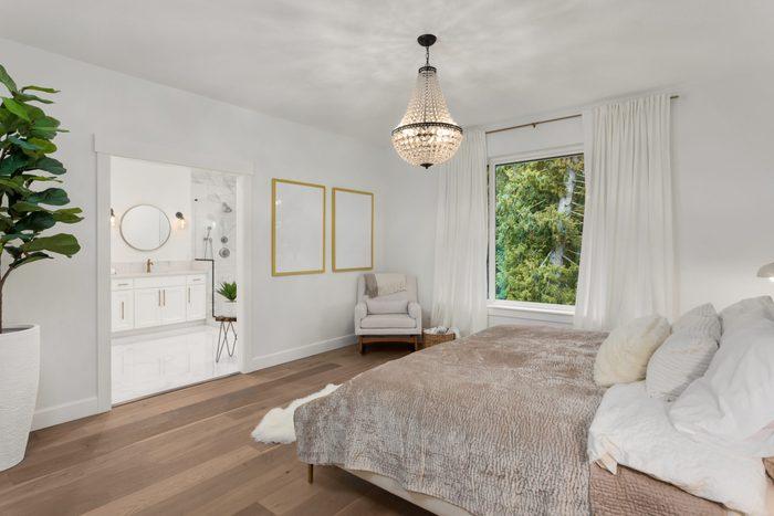 Beautiful Master Bedroom in New Luxury Home. Features Elegant Pendant Light, Hardwood Floors, and View of Ensuite Master Bathroom