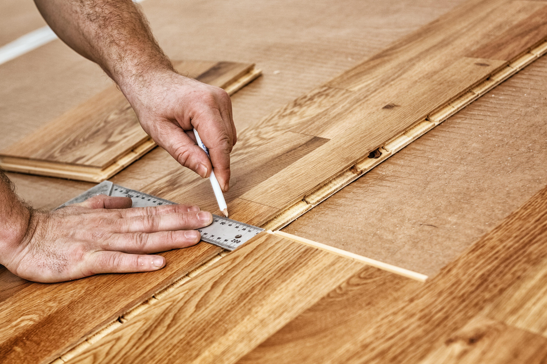 Craftsman installing engineered click system oak wood flooring