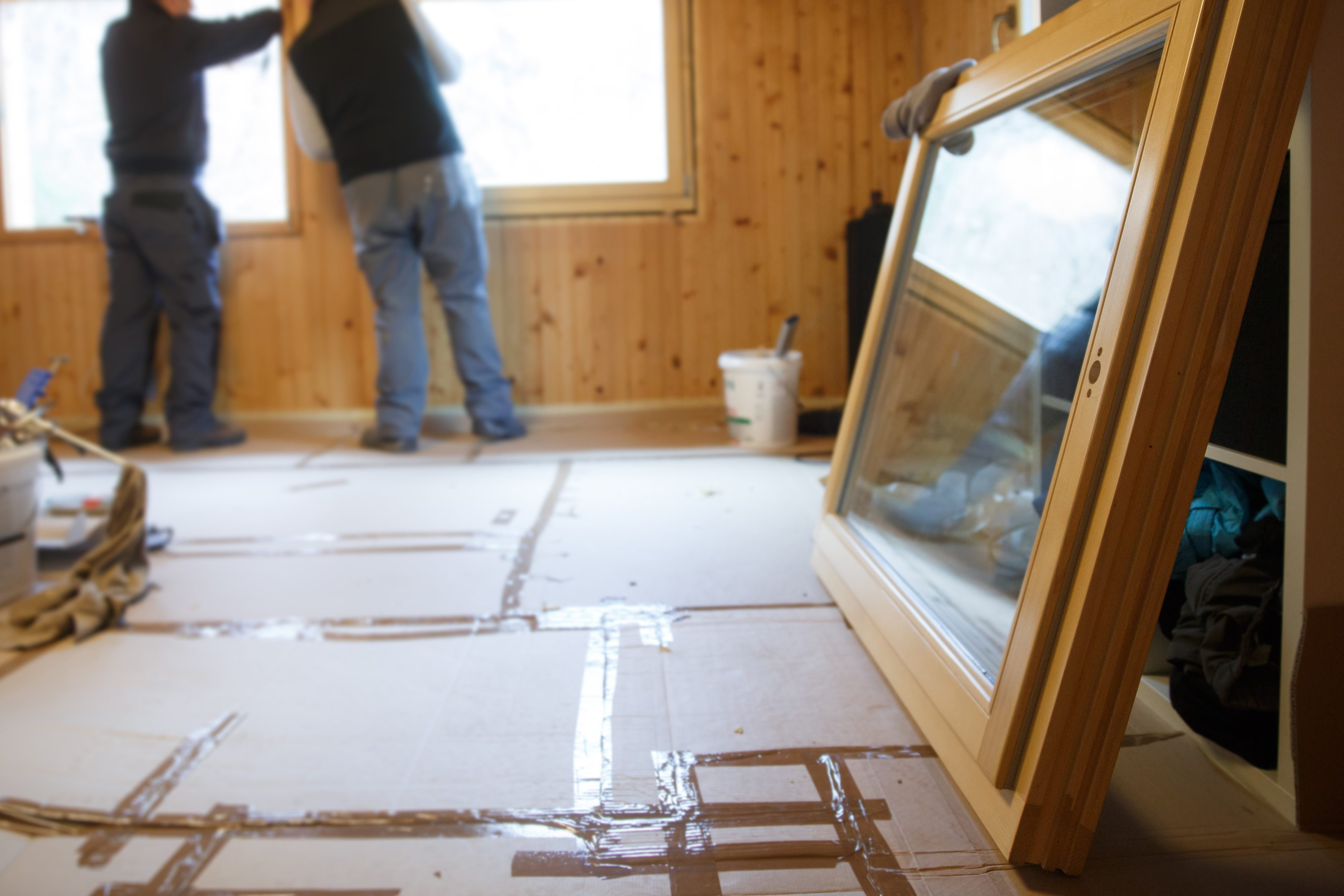 Workers in the background installing new, three pane wooden windows in an old wooden house, with a new window in the foreground. Home renovation, sustainable living, energy efficiency concept.