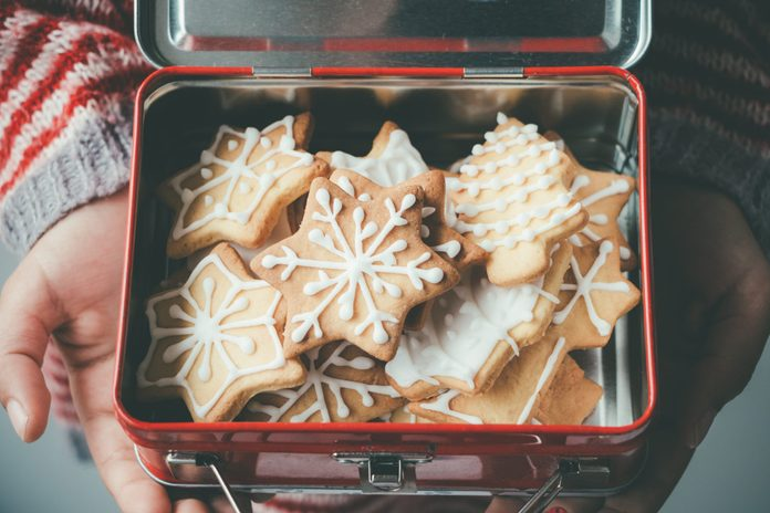 Child hands holding a vintage lunch box full of decorated Christmas cookies