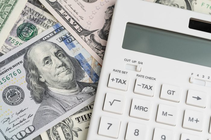 Flat lay or top view of clean white calculator with tax plus and tax minus buttons on pile of US Dollar banknotes money using as tax calculation, budget, investment or financial activities concept.
