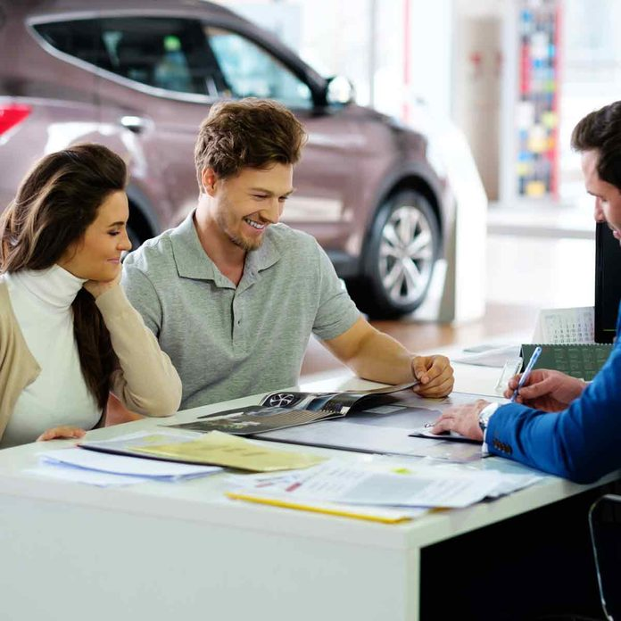 Beautiful-young-couple-reading-a-booklet-at-the-dealership-showroom