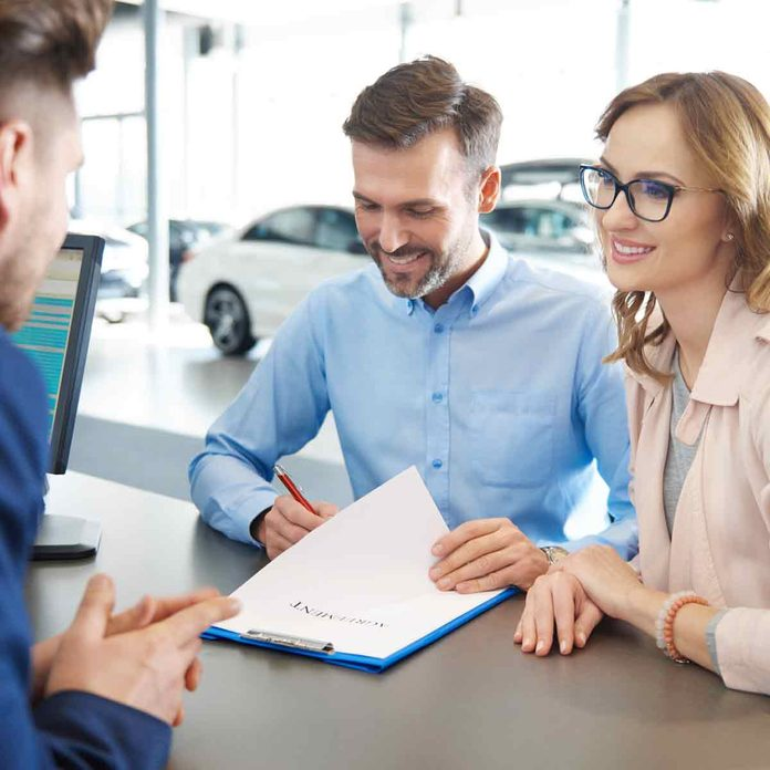 Customers-signing-contract-at-car-dealer-shop