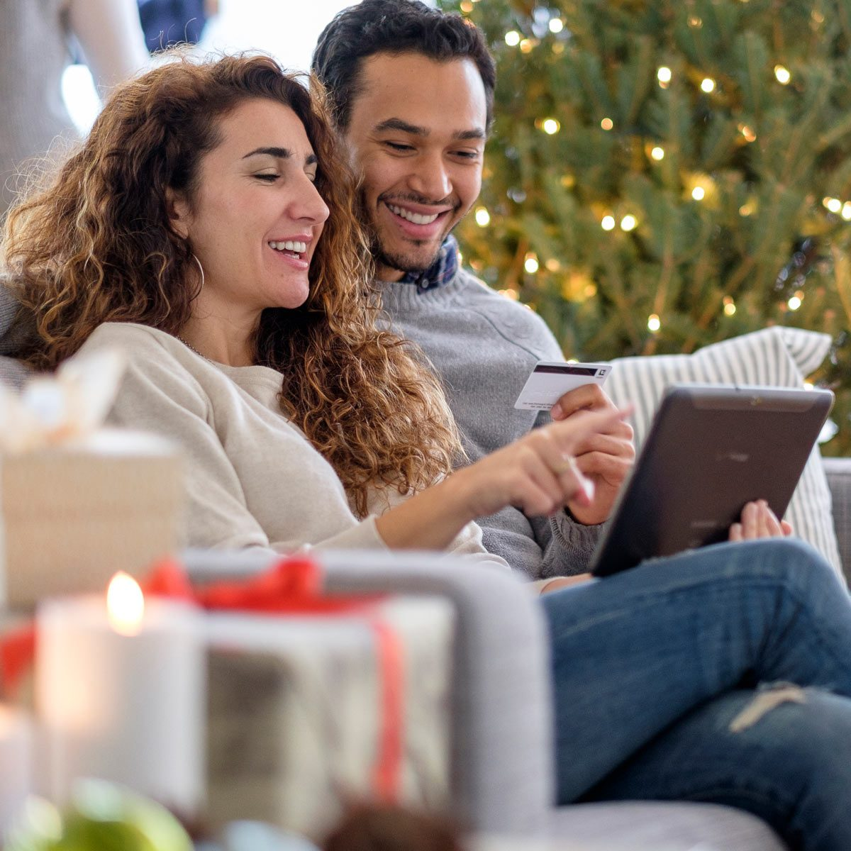 Couple shopping with digital tablet on sofa holiday budget