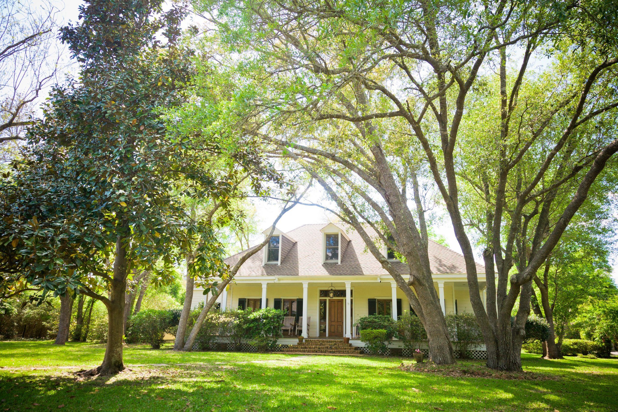 A large ranch style country home with a wrap around porch and dormer windows. The large yard features a mature landscape with trees, bushes and grass.