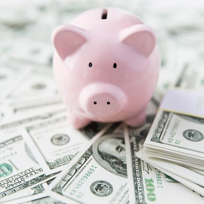 business, finance, investment, saving and corruption concept - close up of dollar cash money and piggy bank on table