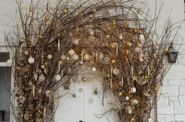 Christmas decorations with natural details: branches with garland lights and christmas balls. Eco decor in interior concept. Creative christmas tree.