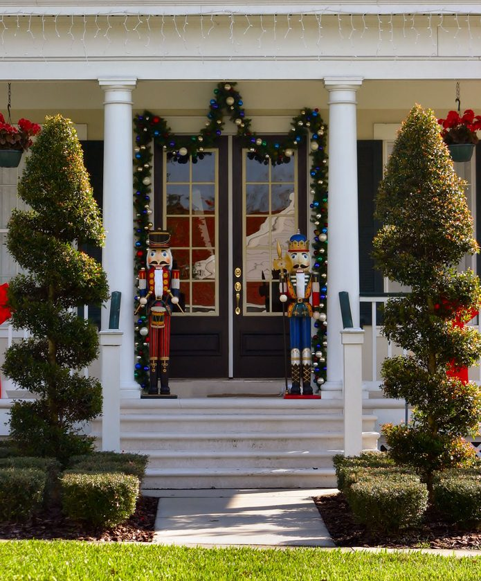 toy soldier christmas decoration on front porch with topiearies
