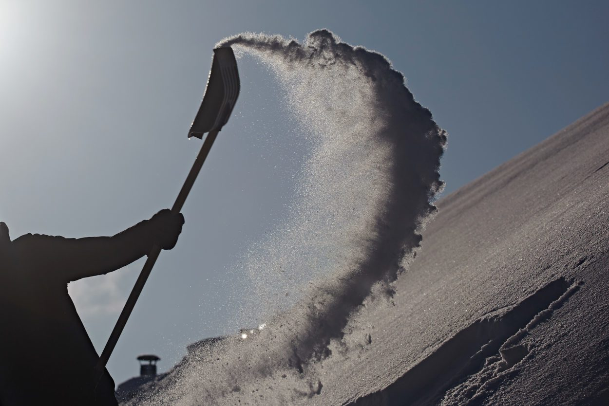 Throwing snow with a snowshovel against blue sky and sun. Silhouette of a man at work.