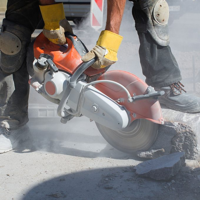 man sawing into block of concrete with large saw