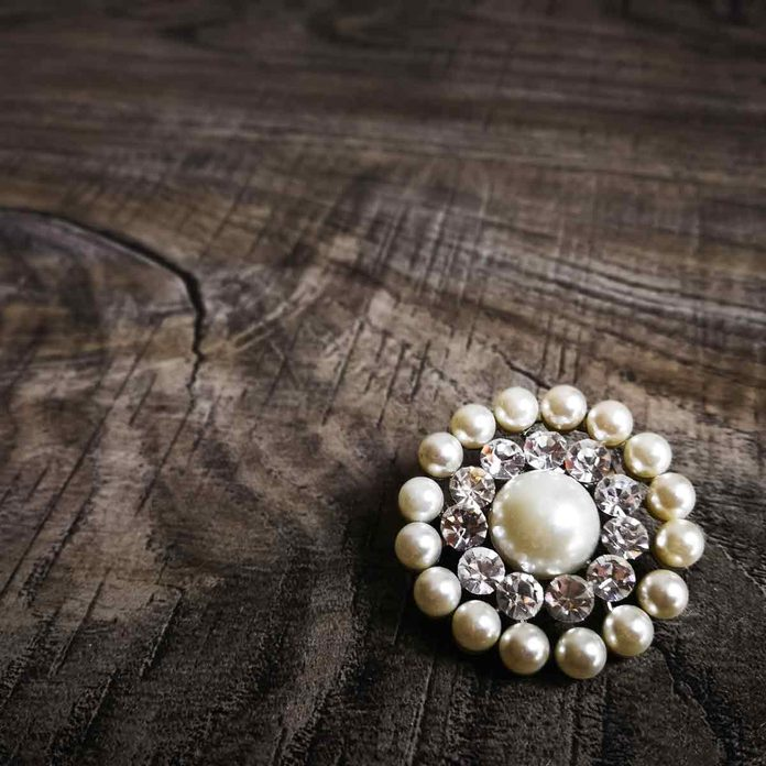 Brooch-with-white-pearl-for-clothes-isolated-on-wooden-background