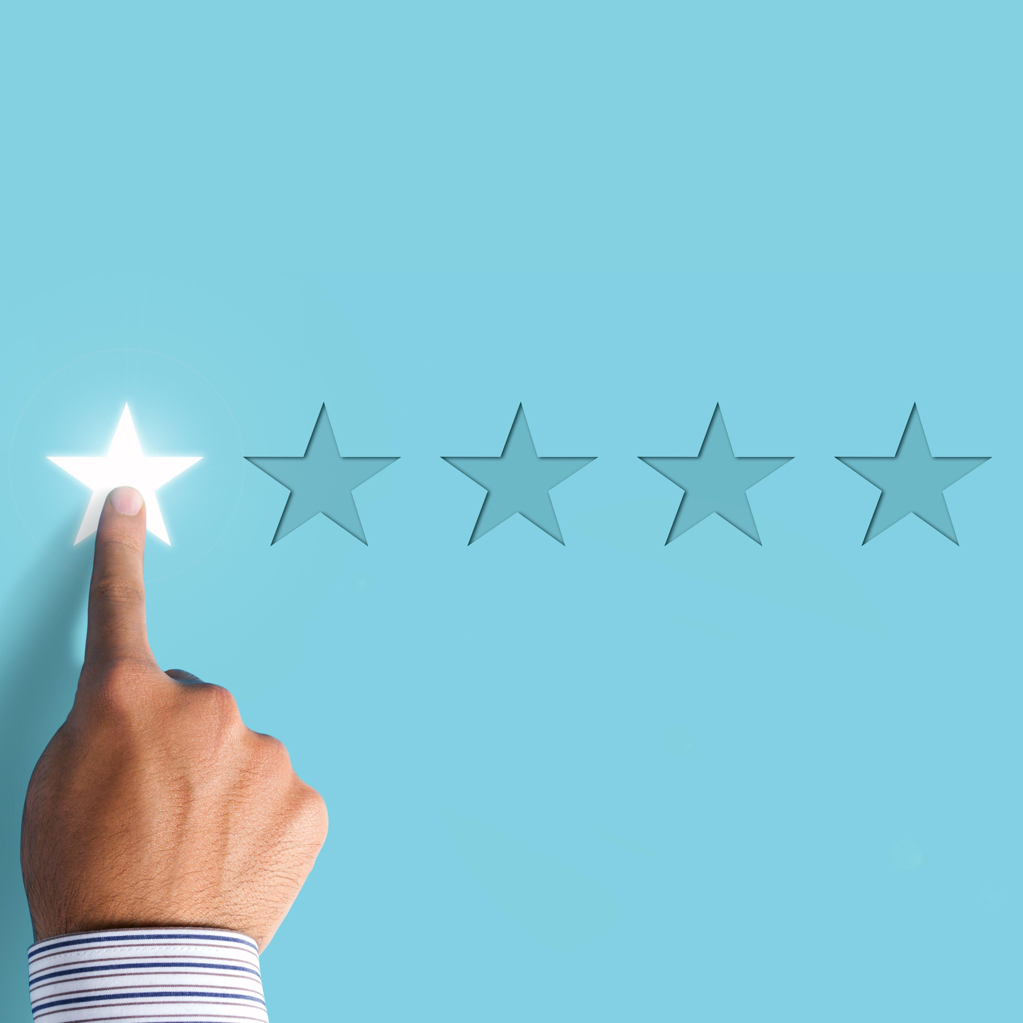 Hand choosing 1 star rating on blue background - negative feedback concept; Shutterstock ID 1129346567; Job (TFH, TOH, RD, BNB, CWM, CM): RD
