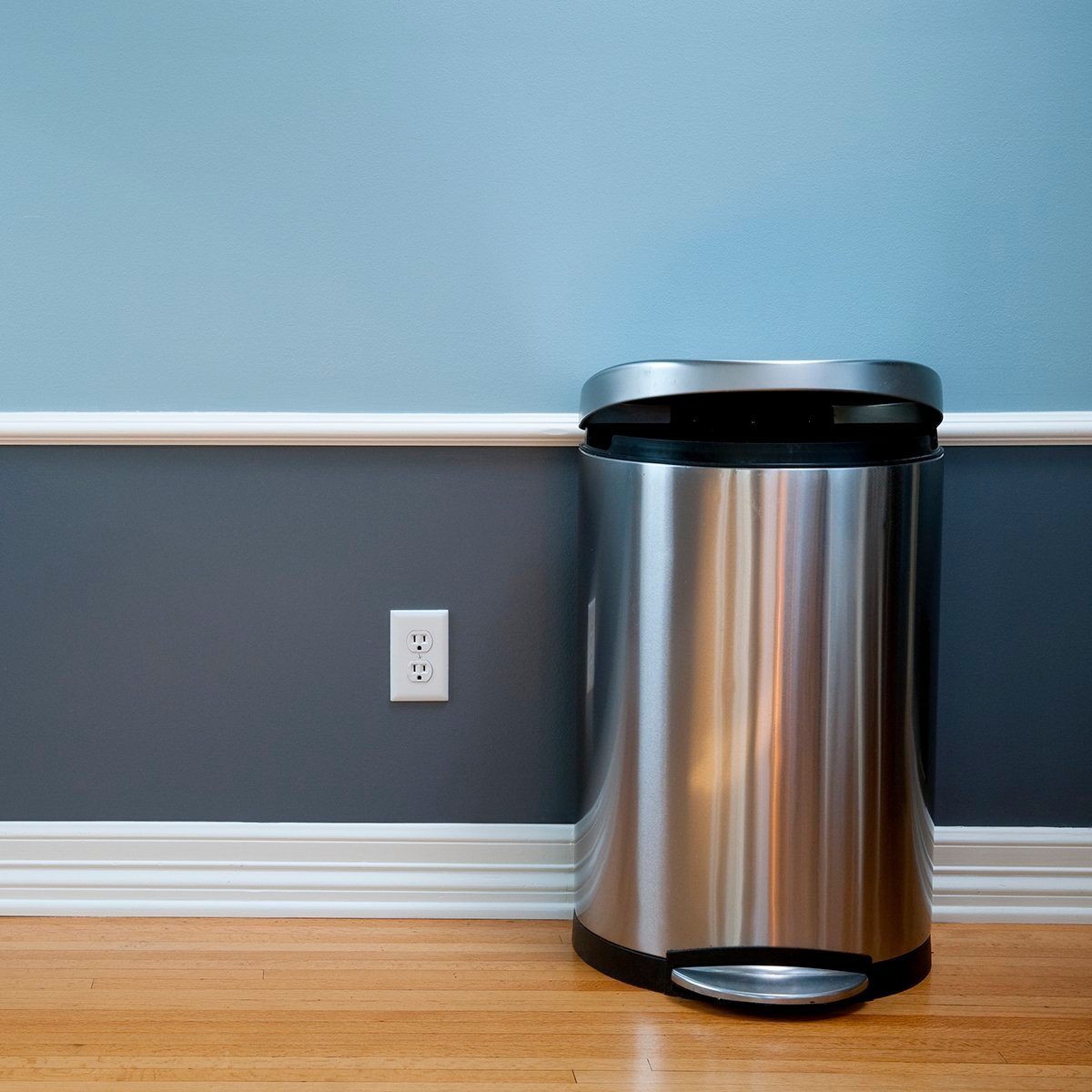 Open trash can in empty room with wood flooring, blue wainscoting and a power outlet.