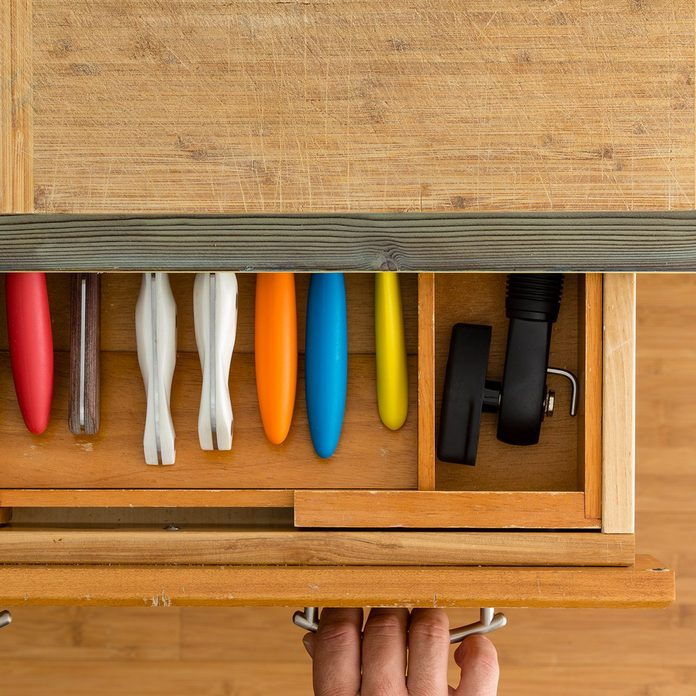 Man or chef opening a knife drawer in a kitchen in an overhead view of the neatly fitted interior of the drawer and a kitchen counter with cutting board