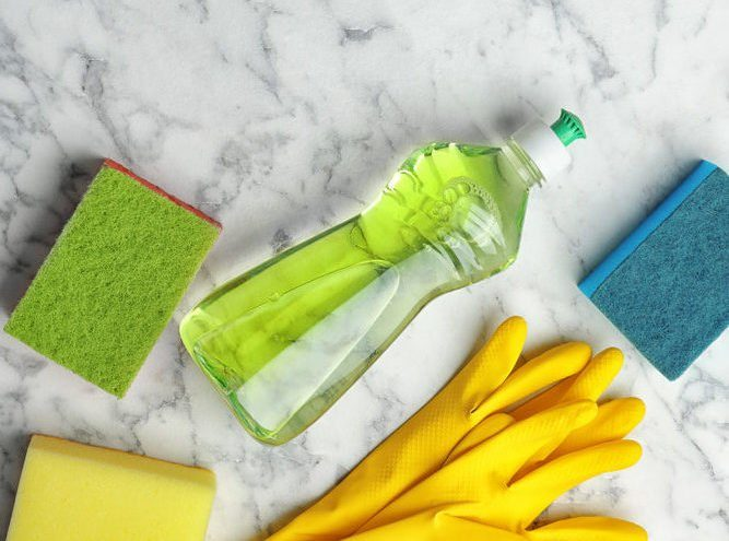 Flat lay composition with cleaning supplies for dish washing and space for text on marble background