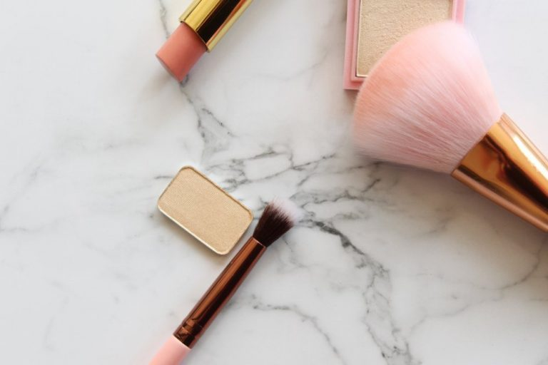 Gold and pink makeup objects against white marble copy space.