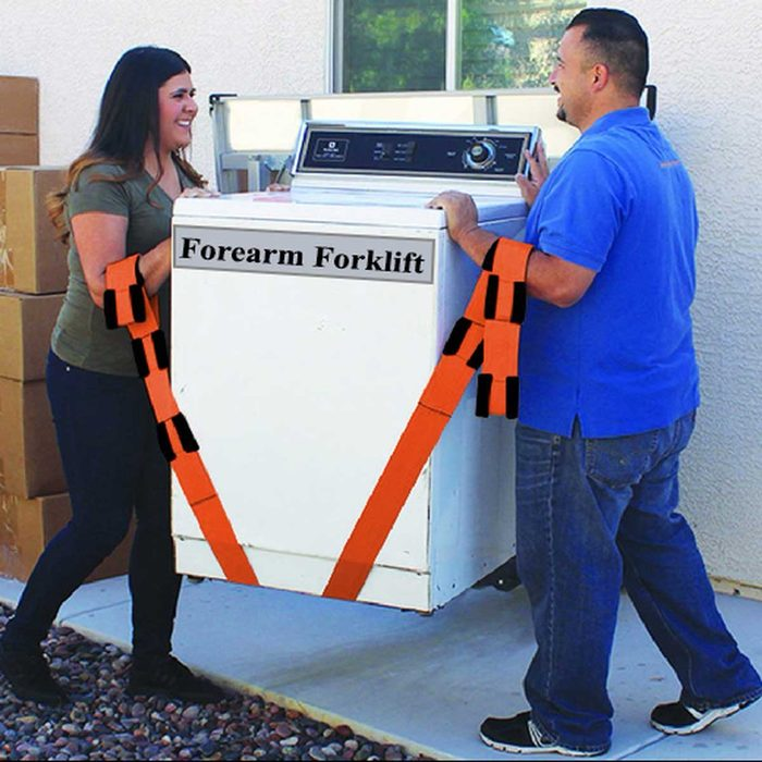 Two people using a Forearm Forklift to move a washing machine