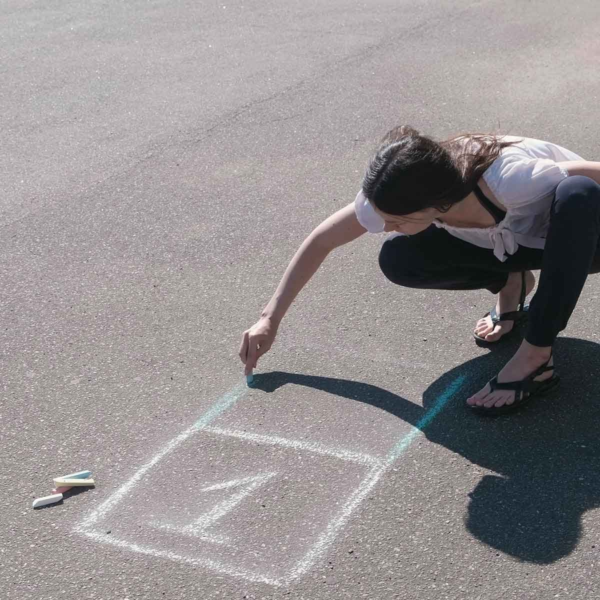 Woman drawing an agility ladder with chalk