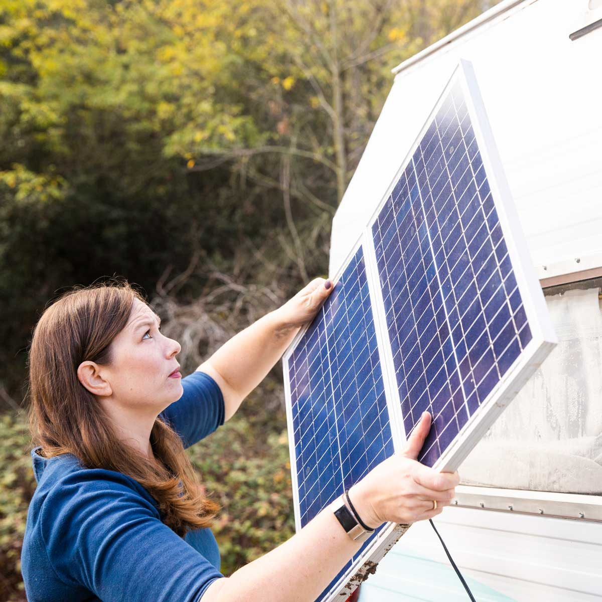 Woman adding solar panels to an RV