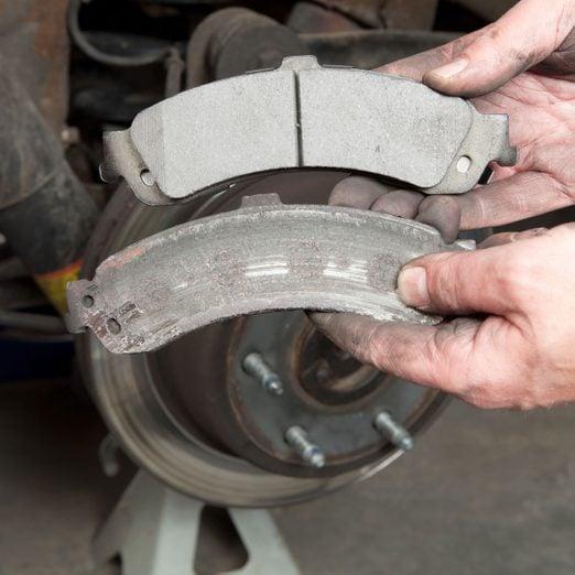 Photo of a worn rear brake pad next to a new rear brake pad