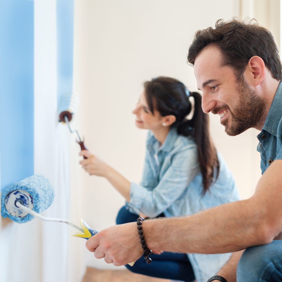 Young couple painting walls in their new house, do it yourself concept