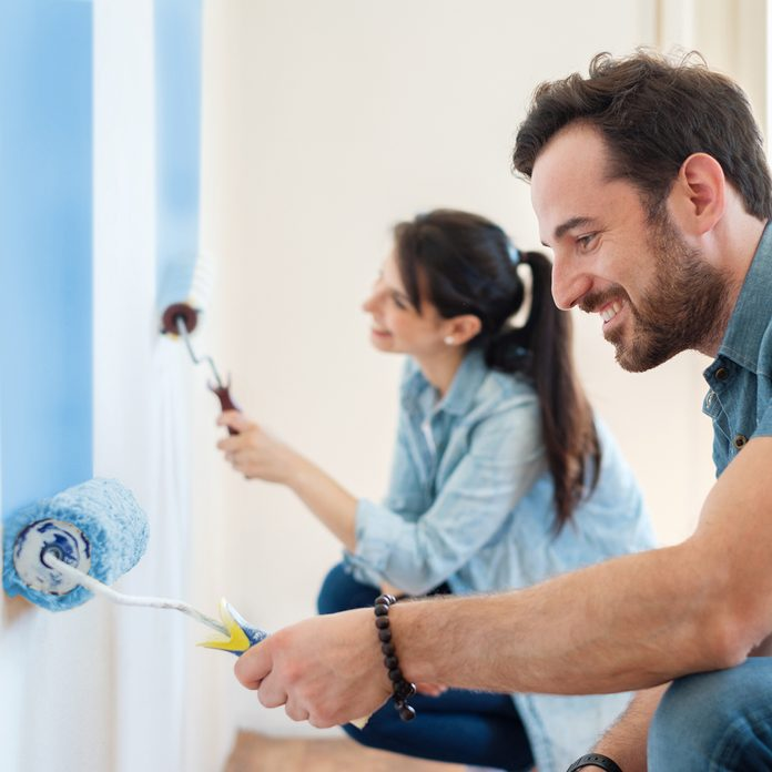 Young Couple Painting Walls In New Home