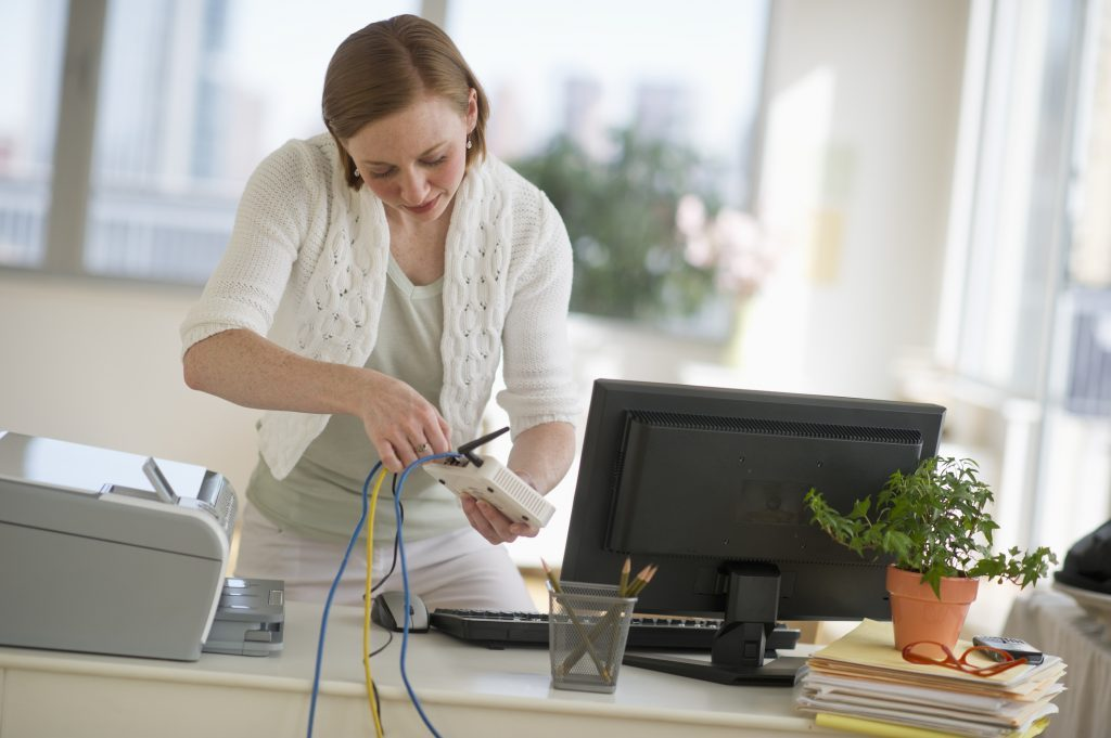 USA, New Jersey, Jersey City, woman installing router at home office