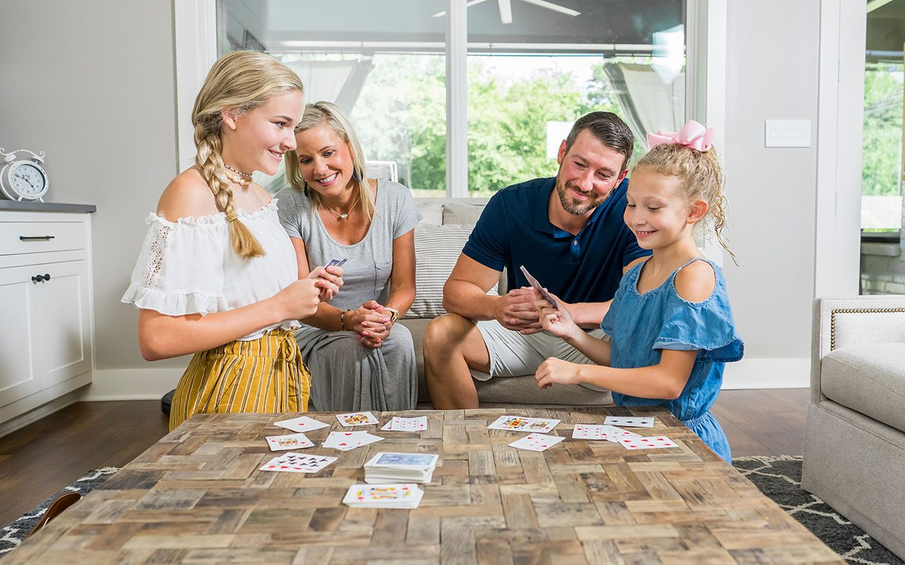 Family sitting around a table playing cards