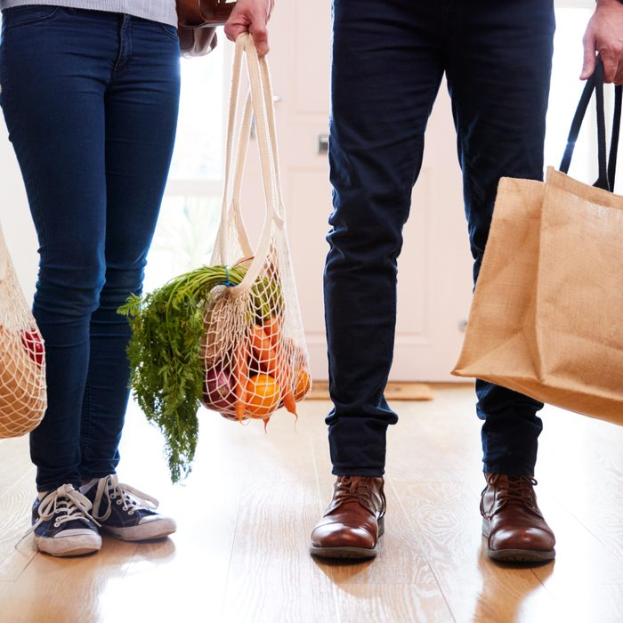 Close Up Of Couple Returning Home From Shopping Trip Carrying Groceries In Plastic Free Bags