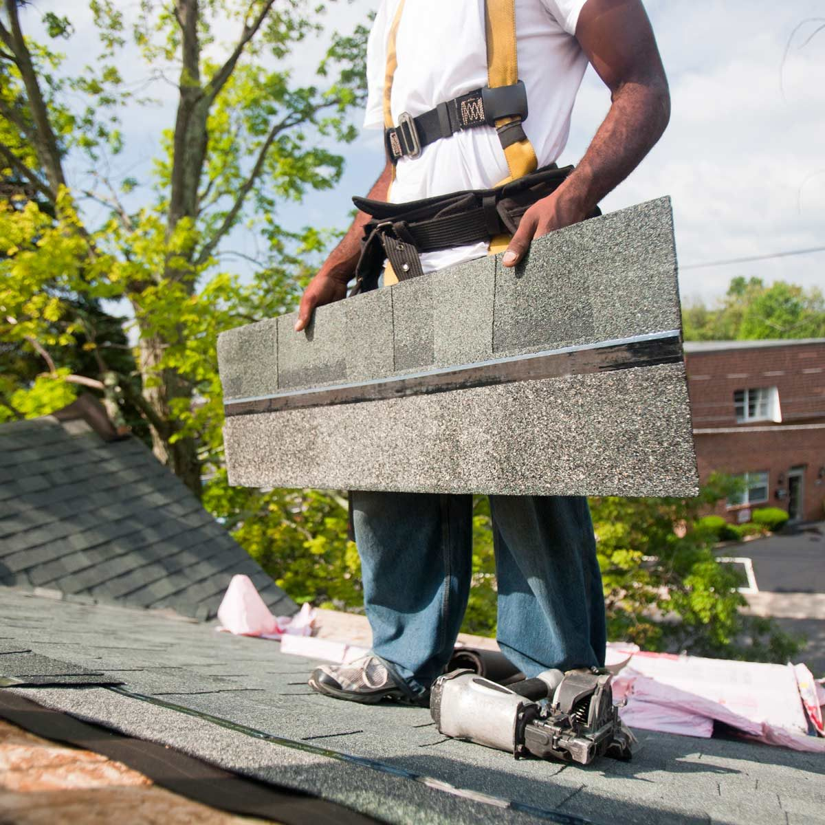 Carpenter aligning shingles on the new roof