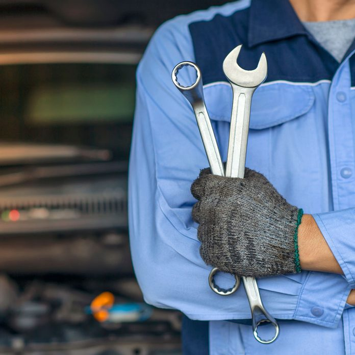 Mechanic holding wrenches