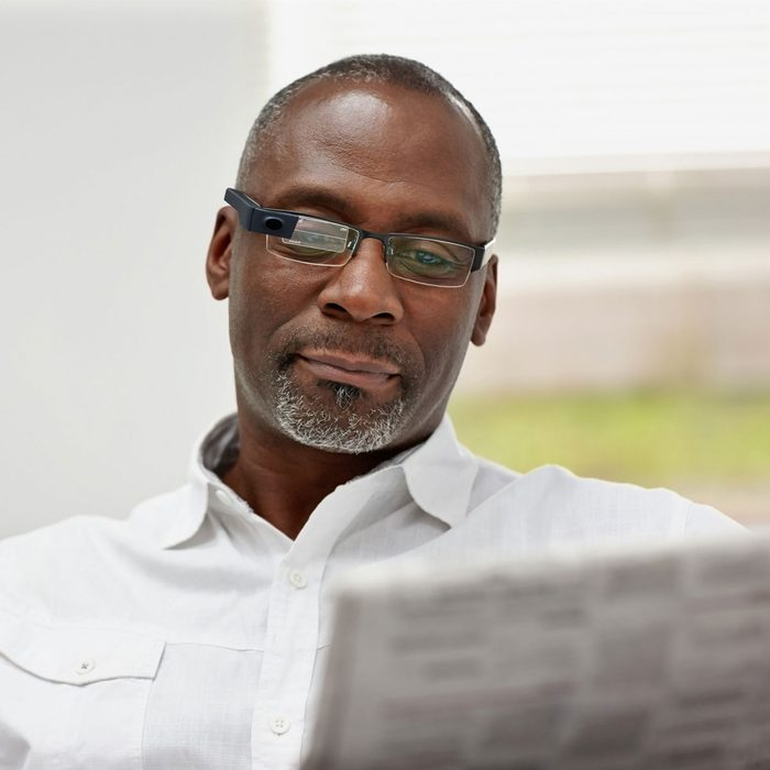 Man reading newspaper with smart glasses