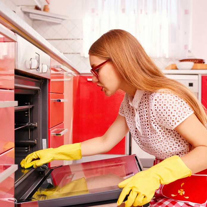 Woman cleaning a red oven