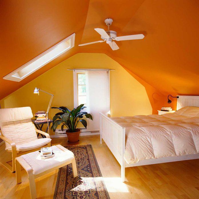 Orange bedroom with a ceiling fan