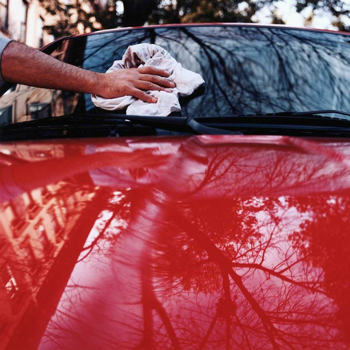 Man wiping a shiny red car