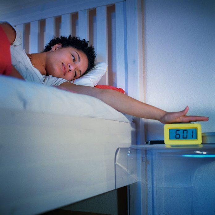 Teenager turning off an alarm clock