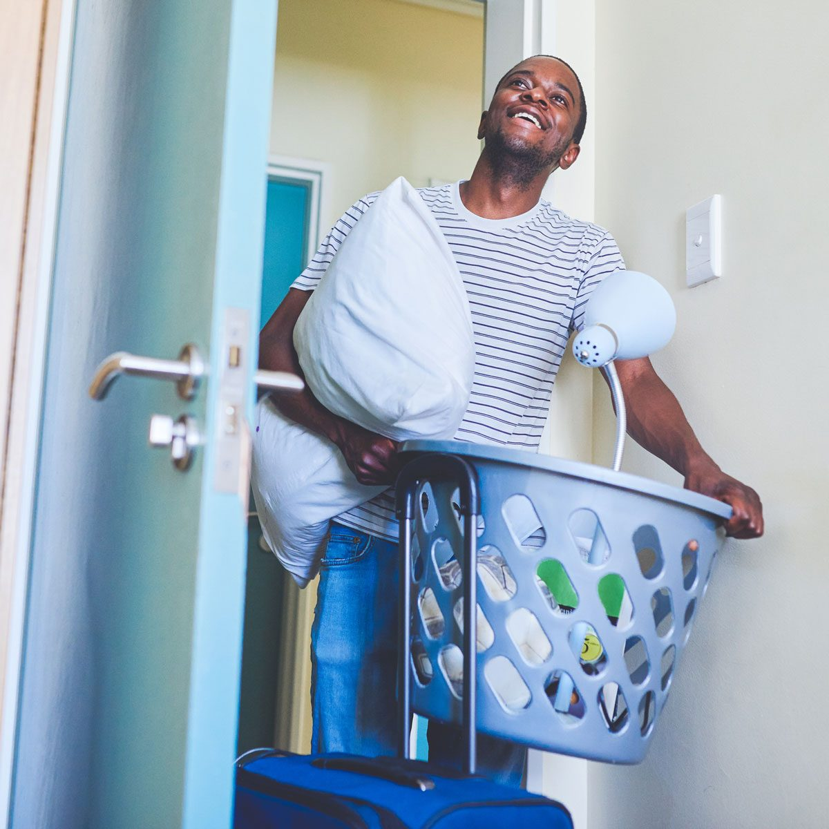 Student with a laundry basket of dorm supplies