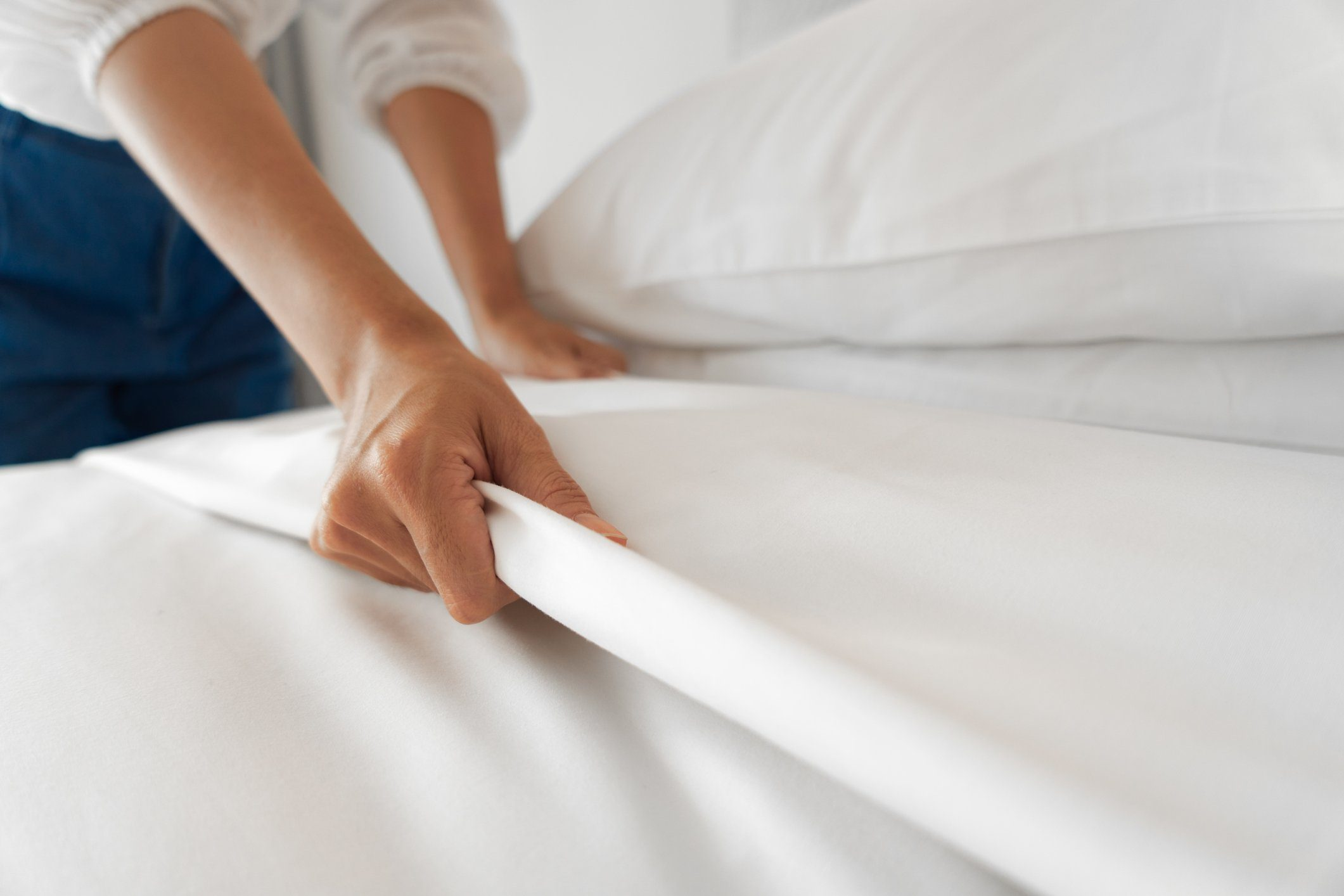 Female Hand set up white bed sheet in bedroom