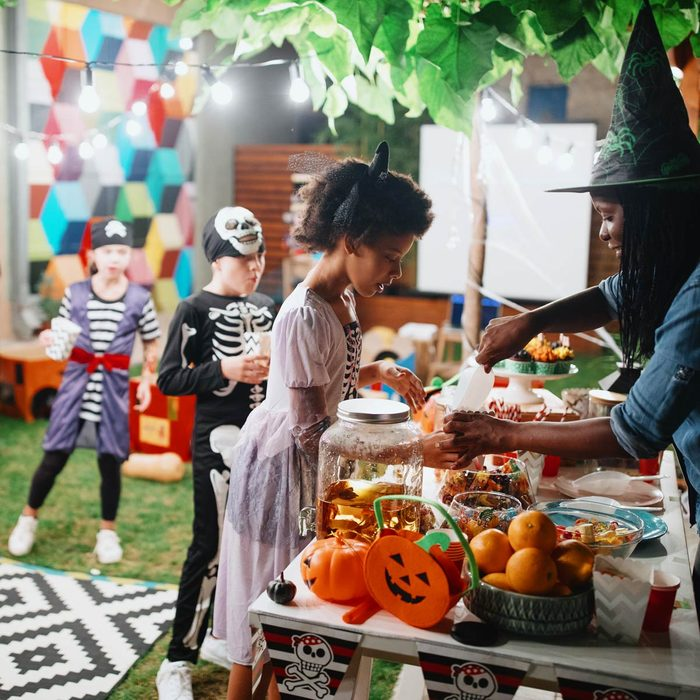 Parent serving candy and popcorn to her kids and their friends halloween party