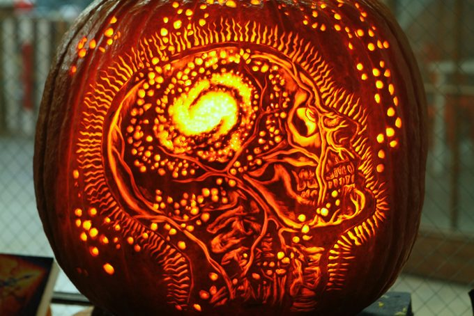 Intricately carved pumpkin of a human profile with the skull inside visible