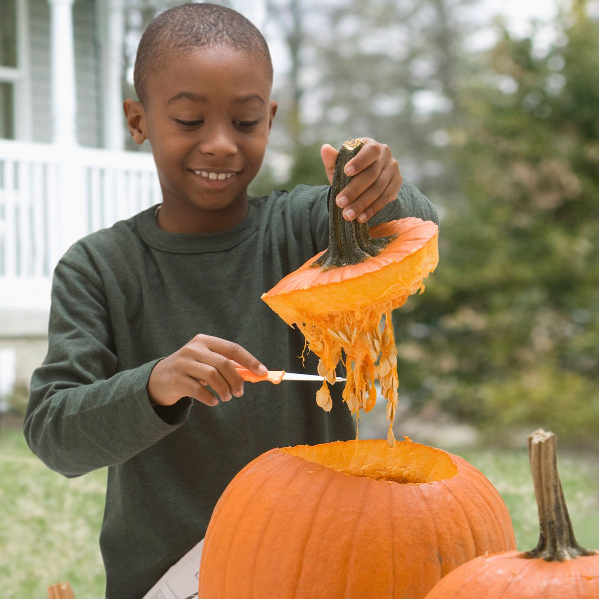 Kid carving a pumpkin