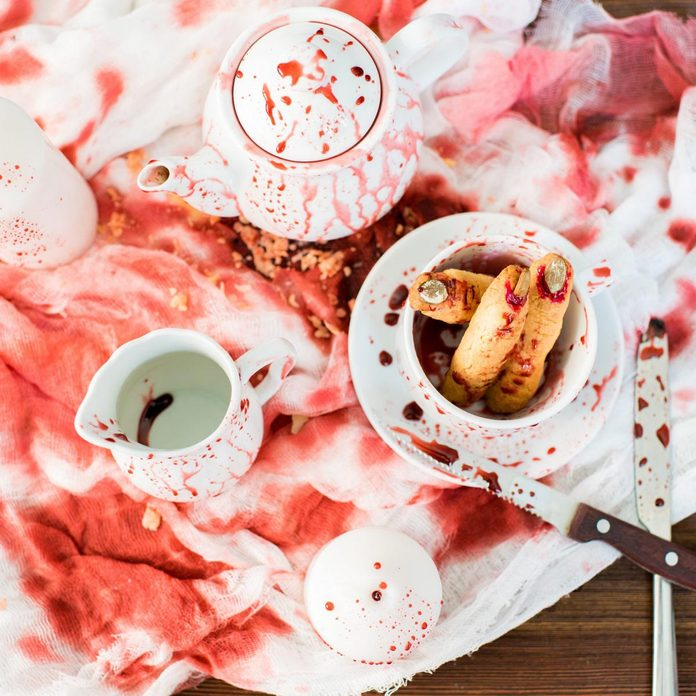 Bloody Halloween composition: high angle view of ceramic crockery in blood placed on dirty gauze, witch finger cookies in bloody cup