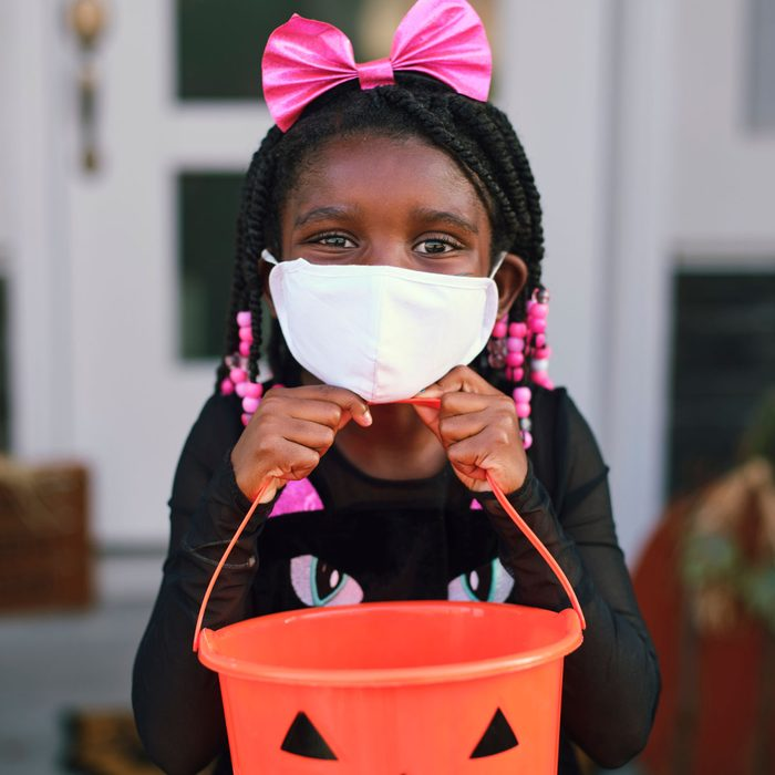 Girl wearing a face mask trick or treating
