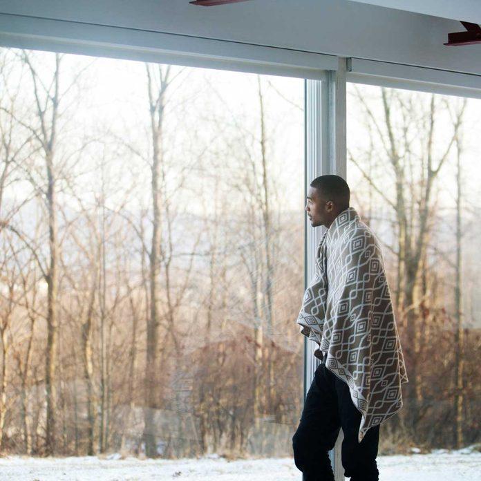 Man wearing a blanket by a window