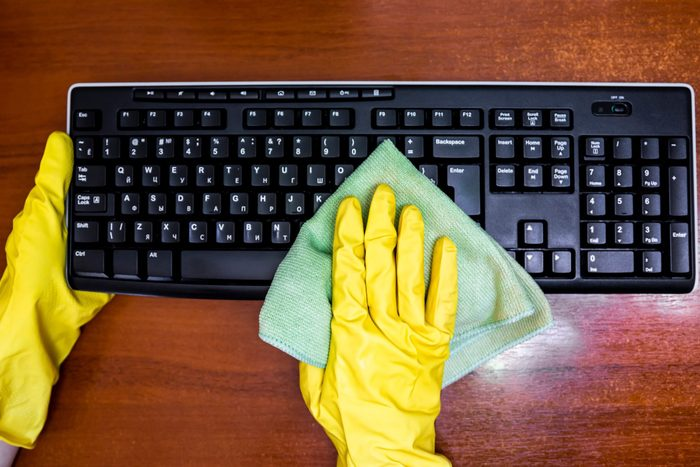 Woman in rubber gloves disinfects the keyboard