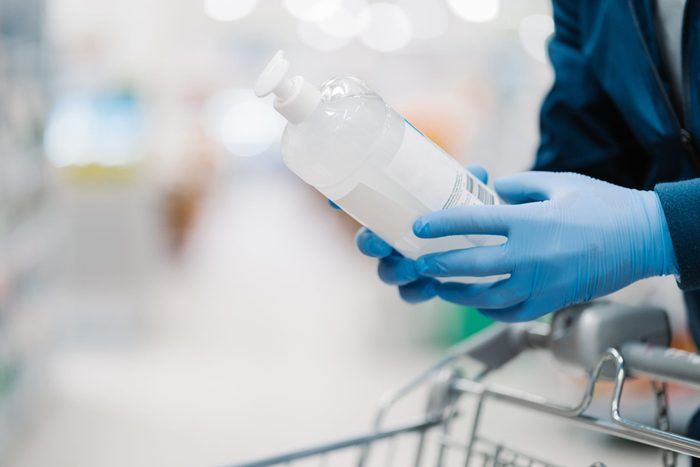 Unrecognizable person in medical gloves holds bottle of sanitizer gel, poses in shop, leans at shopping cart, buys product for coronavirus protection, blurred background. Disinfection, prevention