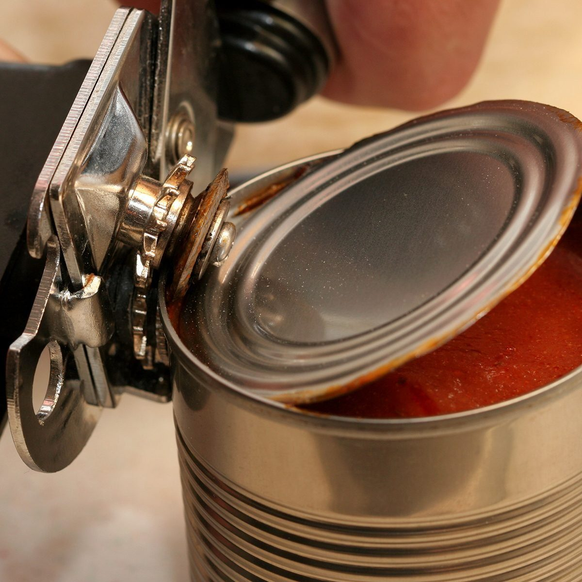 can opener opening can of tomato sauce