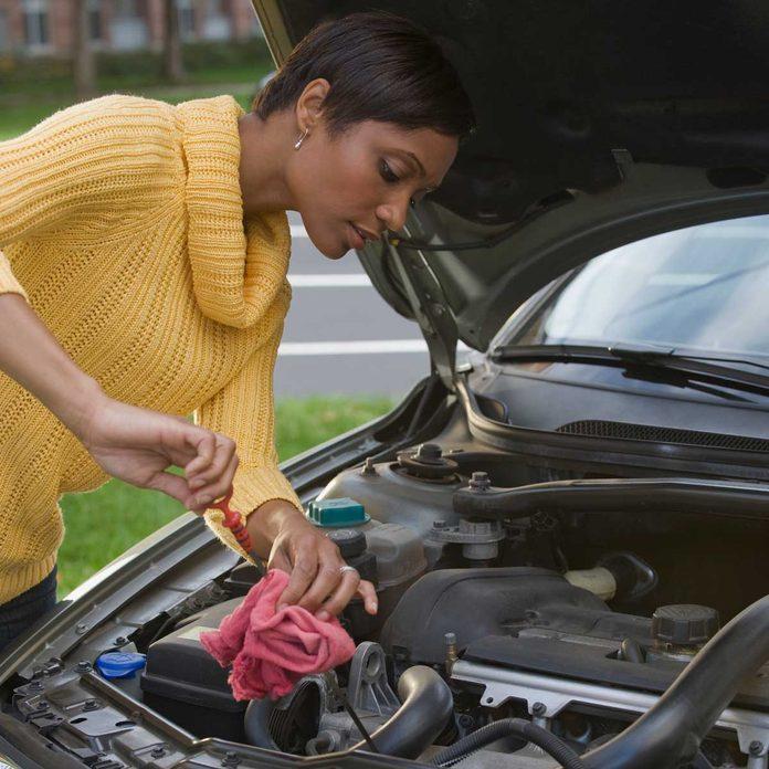 Woman checking car oil